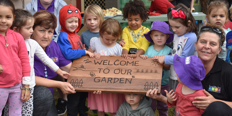 Large group of children holding a sign that says welcome to our garden.